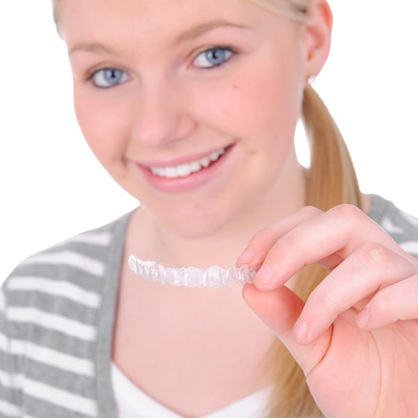 A teenage woman holding her Invisalign clear aligners in front of her