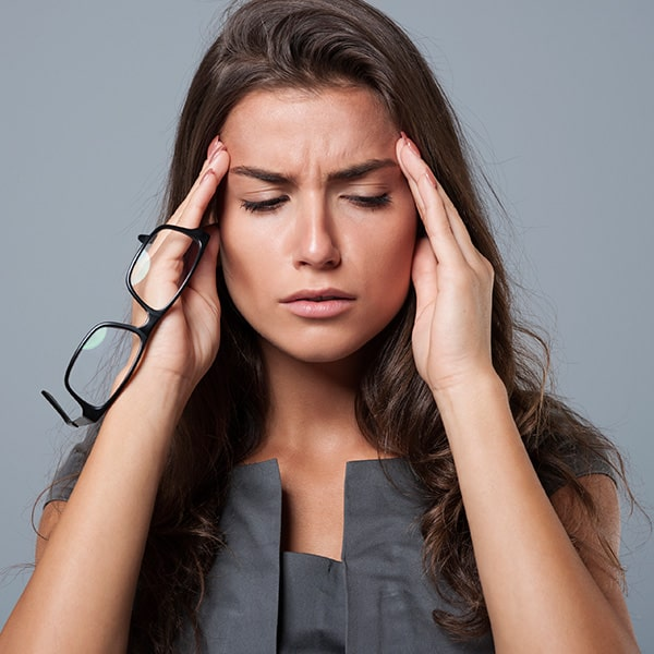 A woman holding her head because of a headache