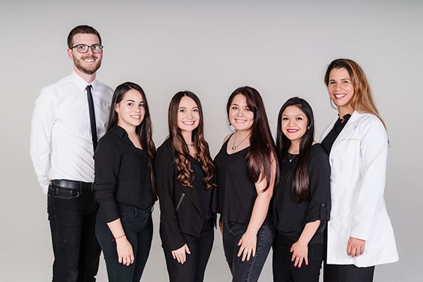 The Spartan Family Dentistry team standing in front of a grey background