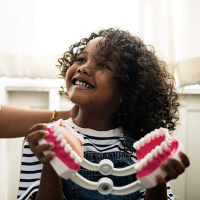 A little girl at the dentist playing with some toy teeth