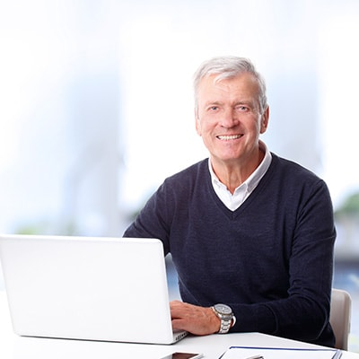 An older man smiling while using a laptop