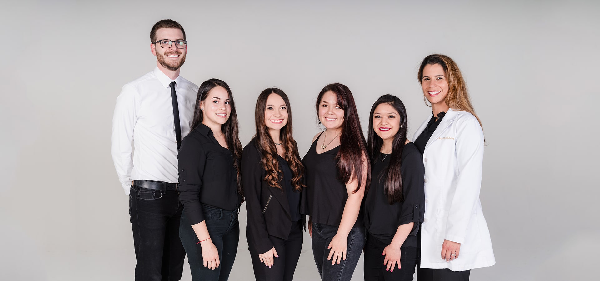 Spartan Family Dentistry team standing in front of a grey background