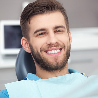 A young man with a beard at the dentist smiling