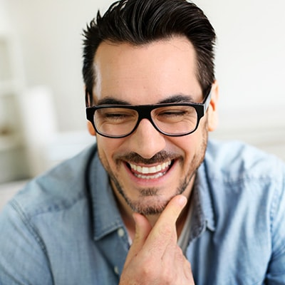 A middle aged man wearing glasses smiling while touching his jaw