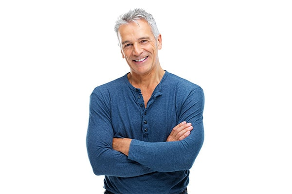 A mature man with dental implants smiling with his arms crossed